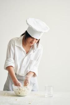 Mulher padeiro com uniforme de cozinheira trabalha com produtos de farinha de massa