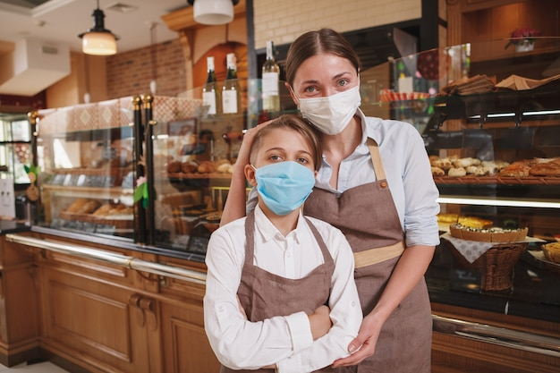 Mulher padeiro feliz e seu filho usando máscaras médicas, trabalhando na padaria da família durante a pandemia de coronavírus
