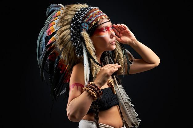 Mulher pagã é uma xamã em estúdio na parede preta, vista lateral feminina com penas no cabelo fazendo ritual