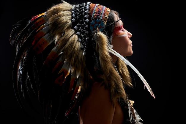 Mulher pagã é uma xamã na parede preta, vista lateral feminina com penas no cabelo fazendo ritual