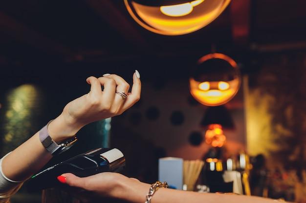 Mulher paga pelo relógio inteligente com tecnologia nfc.