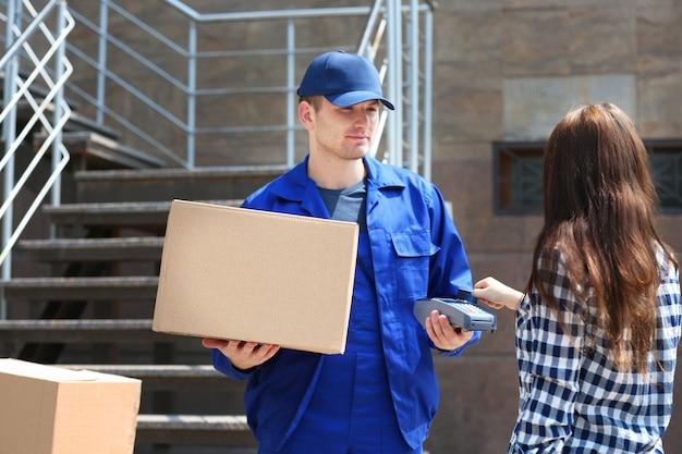 Mulher pagando a entrega com cartão de crédito e terminal de pagamento