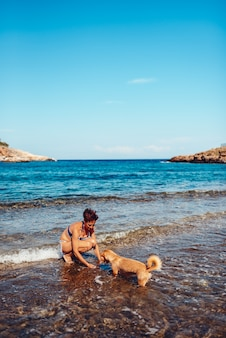 Mulher pagando com um cachorro na praia