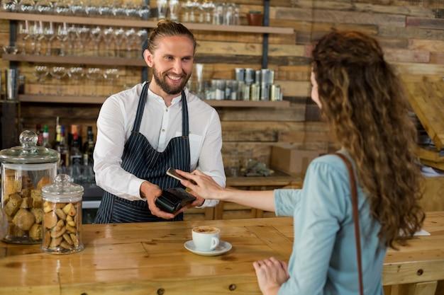 Mulher pagando conta através de smartphone usando a tecnologia nfc