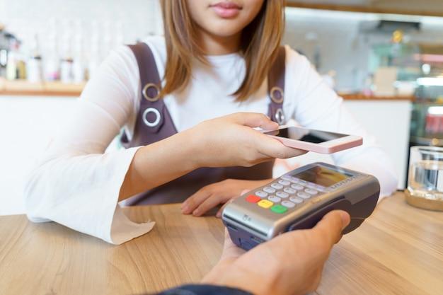 Mulher pagando dinheiro via smartphone com o conceito de cartão magnético.