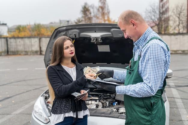 Mulher pagando dólares ao mecânico para diagnóstico do carro