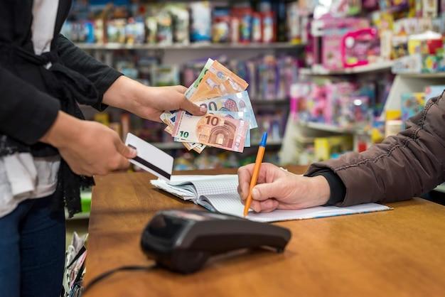 Mulher pagando em uma loja de brinquedos, vendedor escrevendo no diário de vendas