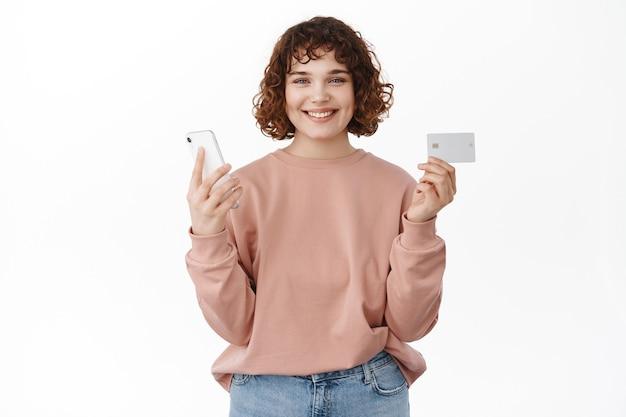 Mulher pagando online, faz pedido no aplicativo móvel, em pé no branco