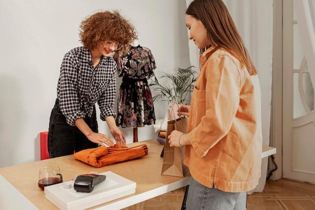 Mulher pagando roupas na loja