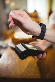 Mulher pagar a factura através smartwatch usando a tecnologia nfc