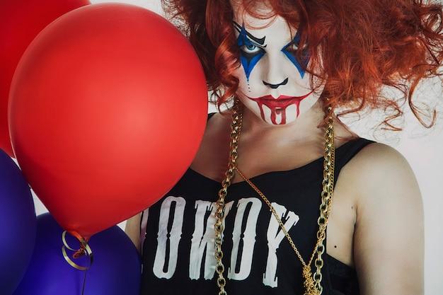 Mulher, palhaço ruivo com um balão, o dia das bruxas