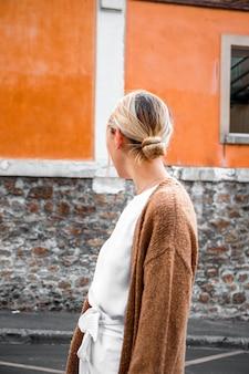 Mulher parada na calçada de frente para o lado