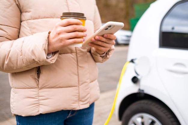Mulher parada perto de carregar um carro elétrico, bebendo café e usando o smartphone
