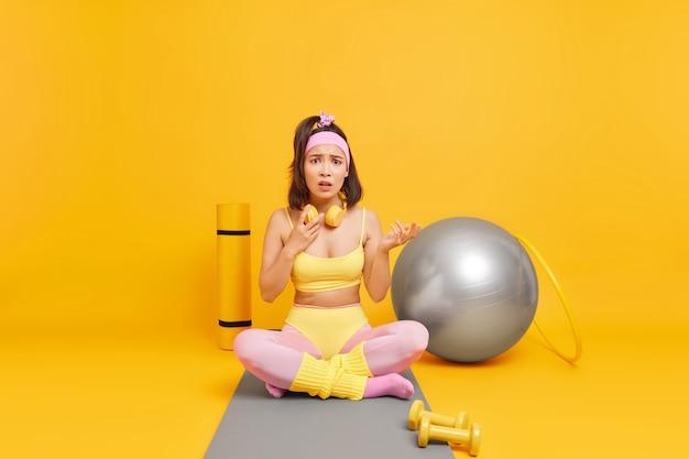 Mulher parece descontente, senta-se com as pernas cruzadas no tapete de fitness e faz exercícios regulares com poses de bola de pilates
