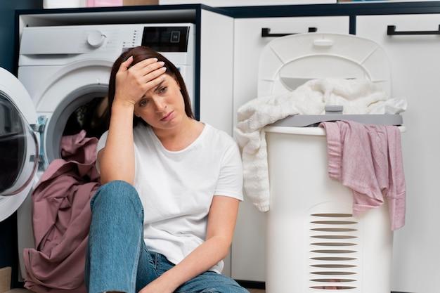 Mulher parecendo cansada depois de lavar a roupa