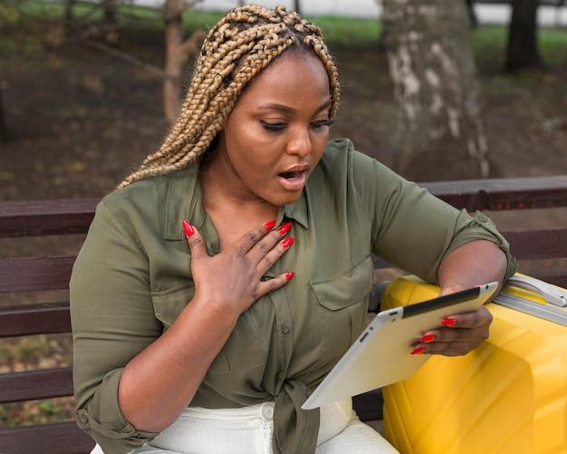 Mulher parecendo chocada com seu tablet lá fora
