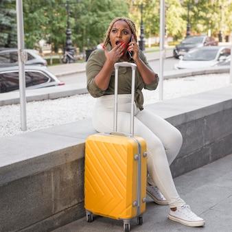 Mulher parecendo chocada enquanto fala ao telefone lá fora