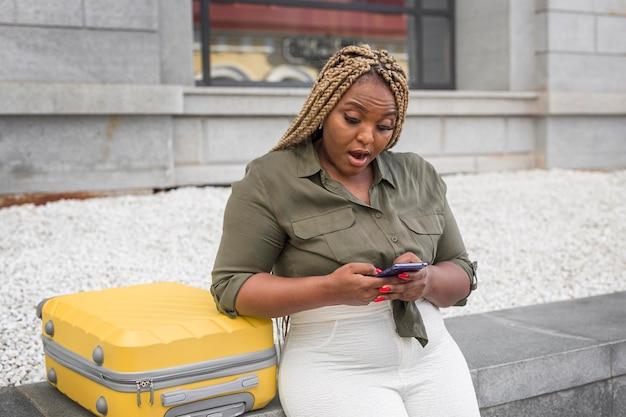 Mulher parecendo chocada enquanto rola a página em um aplicativo de mídia social do lado de fora