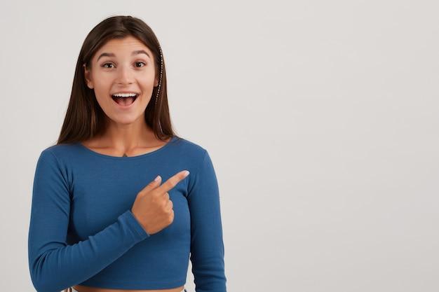 Mulher parecendo feliz, linda garota com cabelo comprido escuro, vestindo um macacão azul