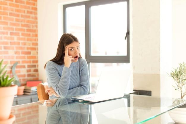 Mulher parecendo surpresa, boquiaberta, chocada, percebendo um novo pensamento, ideia ou conceito
