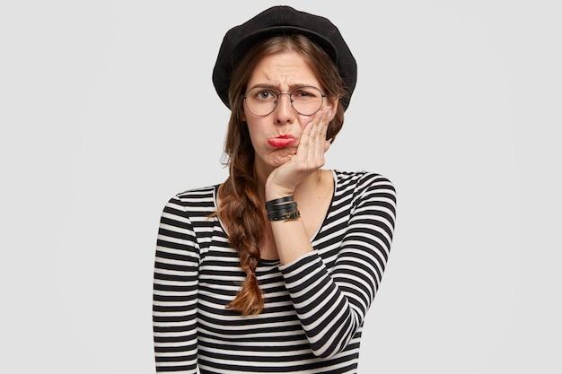 Mulher parisiense descontente franze o lábio inferior e toca a bochecha, tem expressão de tristeza infeliz, insatisfeita com o relacionamento