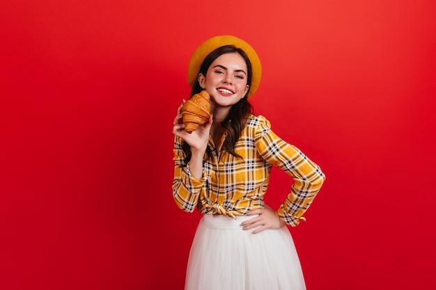 Mulher parisiense em elegante camisa amarela, segurando um croissant apetitoso. senhora de boina com sorriso na parede vermelha.