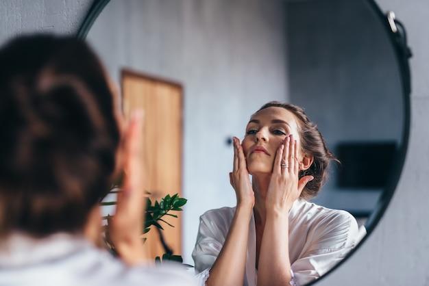 Mulher passa espuma no rosto, limpando a pele.