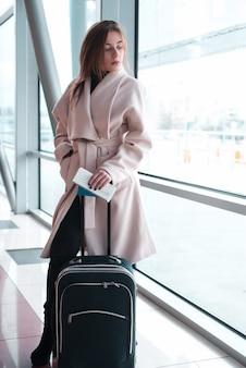 Mulher passageira no aeroporto à espera de viagens aéreas.
