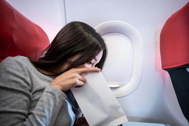 Mulher passageiro no avião vomitado em um saco de papel