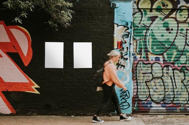 Mulher passando por um mural de arte de rua e pôsteres em branco