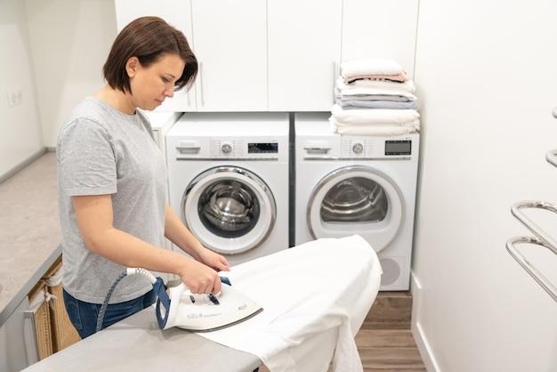 Mulher passando roupa branca a bordo na lavanderia com máquina de lavar roupa