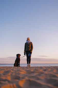 Mulher passeando com o cachorro ao pôr do sol lindo pôr do sol no contexto de edifícios modernos