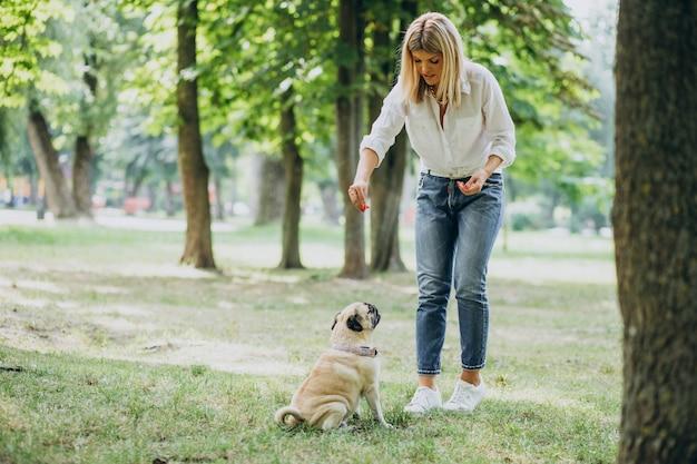 Mulher passeando no parque com seu cachorro pug