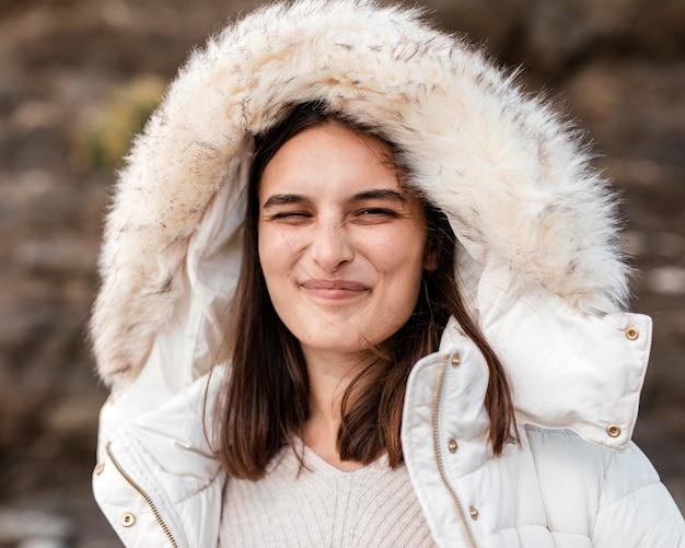 Mulher pateta na praia posando com jaqueta de inverno