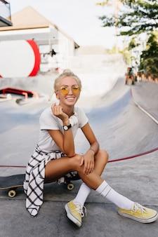 Mulher patinadora satisfeita em relógio de pulso posando com sorriso inspirado. retrato ao ar livre de jovem elegante relaxante no parque de skate em dia de verão.