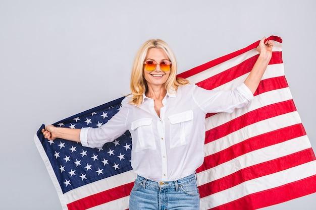 Mulher patriótica bonita sênior sorridente usando a bandeira dos estados unidos isolada sobre um fundo branco com uma cara de surpresa.