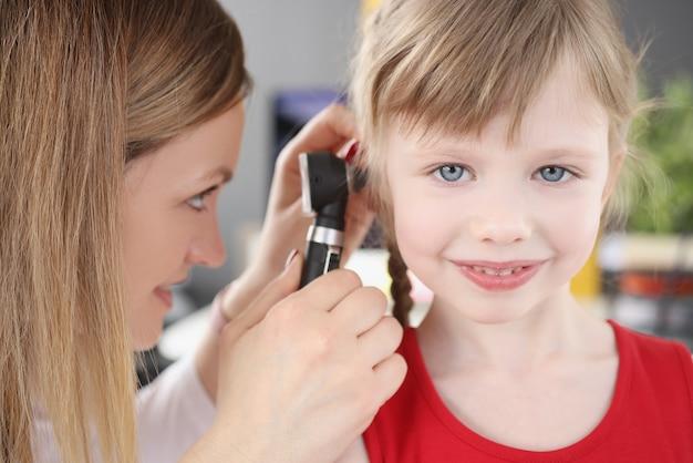 Mulher pediatra olhando para o tímpano da menina usando otoscópio no diagnóstico clínico e