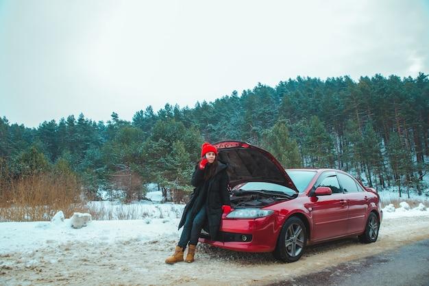 Mulher pedindo ajuda com carro quebrado em rodovia de inverno, parado na beira da estrada