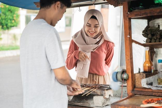 Mulher pedindo espetadas de frango na vendedora de comida de rua