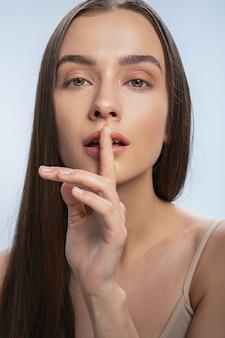 Mulher pedindo silêncio com um gesto de mão