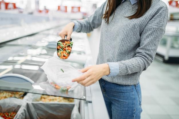 Mulher pega um pacote de vegetais congelados em um supermercado, às compras da família. cliente feminino compra produtos na loja, comprador no mercado