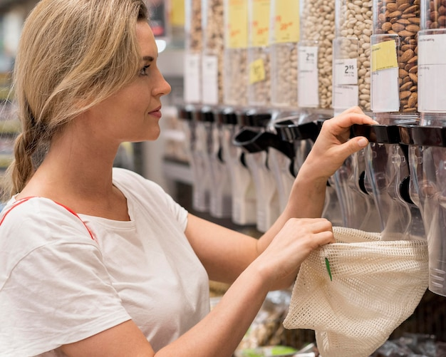 Mulher pegando deliciosas amêndoas do mercado