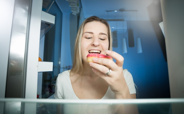 Mulher pegando donut da prateleira da geladeira tarde da noite