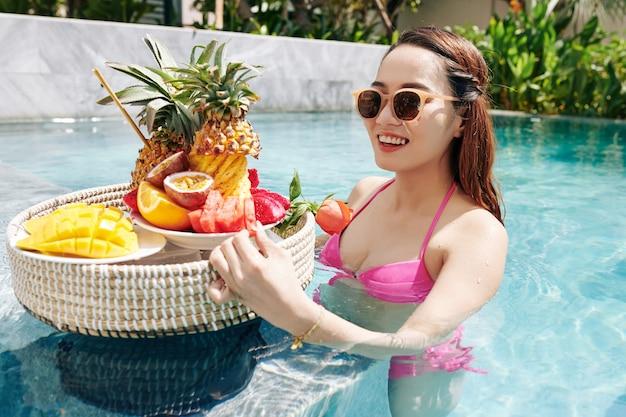 Mulher pegando frutas da bandeja de vime