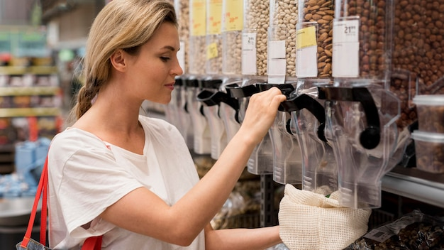 Mulher pegando nozes deliciosas do mercado