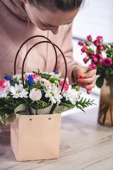 Mulher pegando o buquê de flores diferentes em uma sacola de papel com alças. vertical