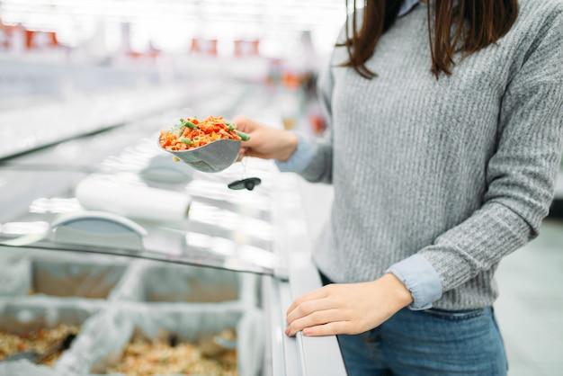 Mulher pegando pacote de vegetais congelados