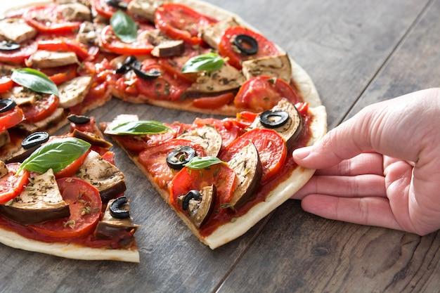 Mulher pegando pizza vegetariana com berinjela, tomate, azeitonas pretas, orégano e manjericão na superfície de madeira