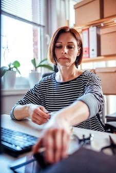 Mulher pegando smartphone no escritório