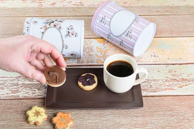 Mulher pegando um biscoito amanteigado coberto de chocolate, ao lado de outros biscoitos, xícara de café e latas deitada.